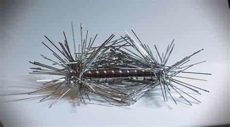 An einem Stabmagnet haben sich an den beiden Polen viele Eisennägel gesammelt.